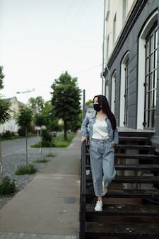 Dziewczyna w masce ochronnej na balkonie patrzy na puste miasto.