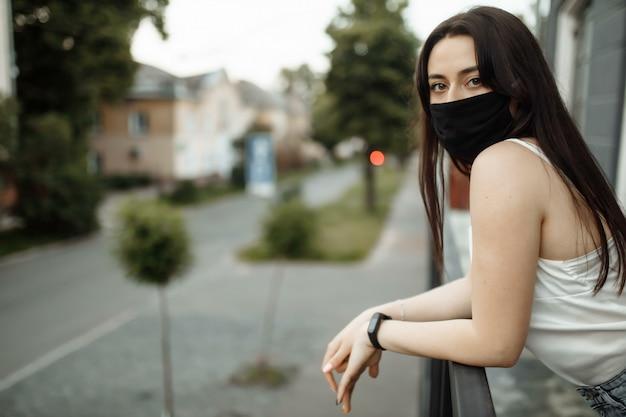 Dziewczyna w masce ochronnej na balkonie patrzy na puste miasto