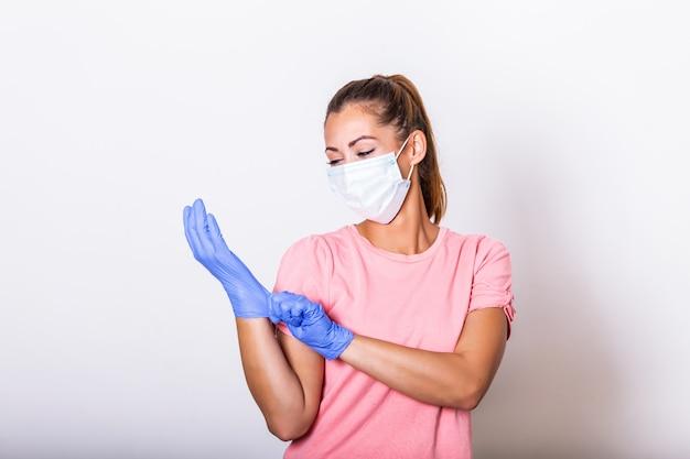 Dziewczyna w masce oddechowej. zamaskowana atrakcyjna kobieta zakłada rękawiczki ochronne. młoda kobieta z maską ochronną