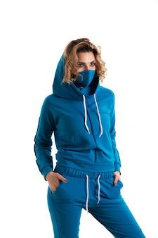 Dziewczyna w masce oddechowej. zamaskowana kobieta patrzy na aparat. przeziębienie, grypa, wirus, zapalenie migdałków, choroby układu oddechowego, kwarantanna, koncepcja epidemii. piękna caucasian młoda kobieta z twarzy maską