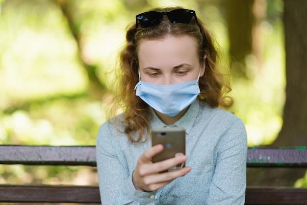 Dziewczyna w masce zdjęła krem przeciwsłoneczny, żeby sprawdzić telefon