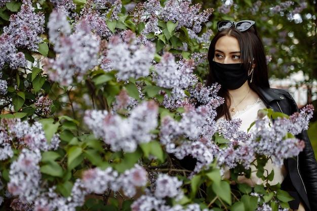 Dziewczyna w medycznej masce na tle kwitnących bzów. czarna maska. ochrona przed wirusem, grypą. koronawirus ochrona. epidemia koronawirusa
