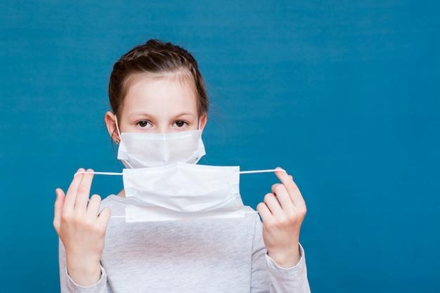 Dziewczyna w medycznej masce nakłada na siebie drugą czystą maskę. ochrona dziecka