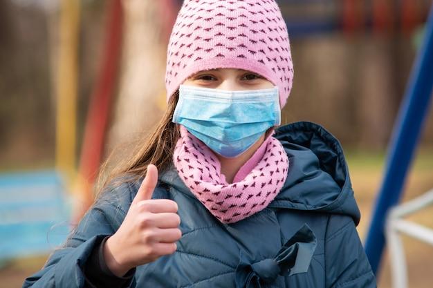 Dziewczyna w medycznej ochrony masce pokazuje kciuk w górę pozyci przed boiskiem plenerowym