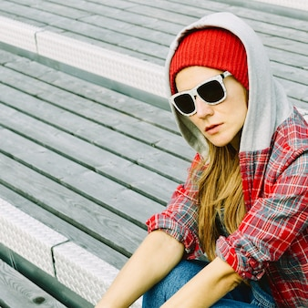 Dziewczyna w miejskich lokalizacjach w czerwonym kapeluszu i modnych okularach przeciwsłonecznych.