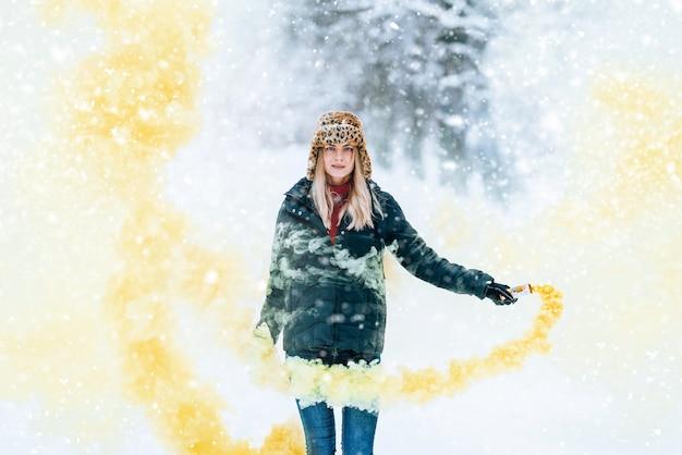 Dziewczyna w modnej czapce zimowej z lampartowym nadrukiem raduje się na śniegu
