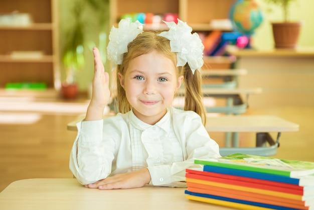 Dziewczyna w mundurku szkolnym siedzi w klasie z książkami. uczeń w klasie w szkole