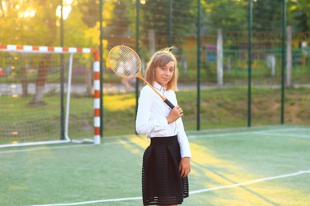 Dziewczyna w mundurku szkolnym z rakietą w dłoniach na boisku.