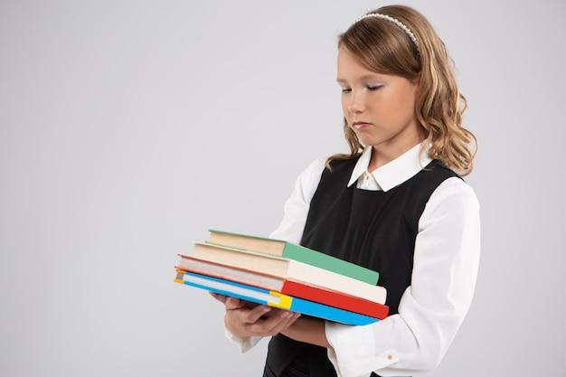 Dziewczyna w mundurku szkolnym ze smutkiem patrzy na stos podręczników, które trzyma w rękach