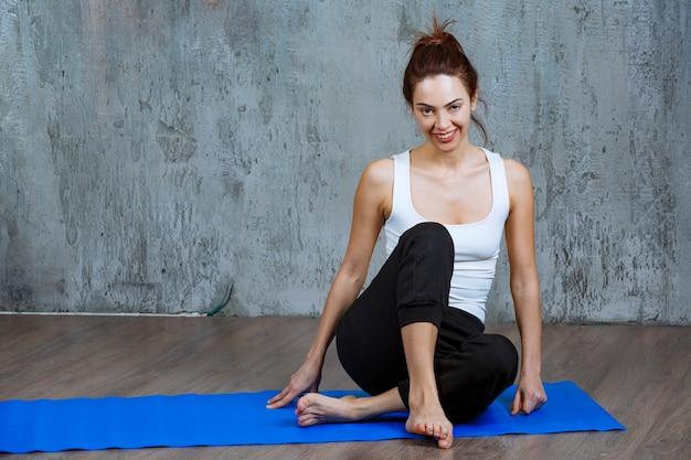 Dziewczyna w mundurze sportowym siedzi na niebieskim matowym jogi po ciężkim treningu.