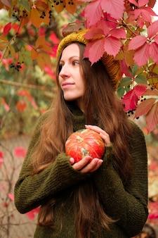 Dziewczyna w musztardowej czapce i zielonym swetrze z wełny bagiennej trzyma małą pomarańczową dynię