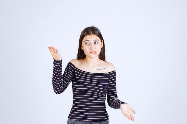 Dziewczyna w myśleniu w paski koszula i burzy mózgów.
