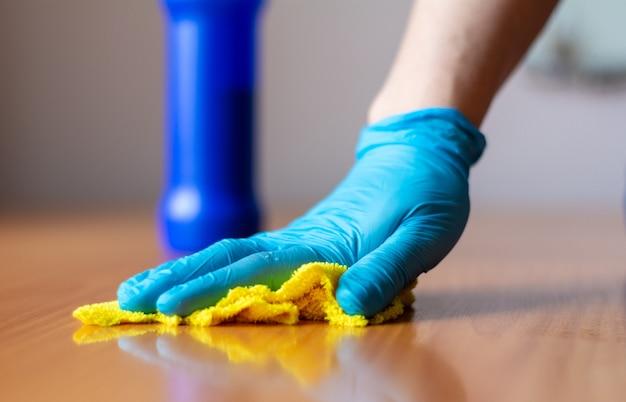 Dziewczyna w niebieskich rękawiczkach myje żółtą szmatą drewniany stół