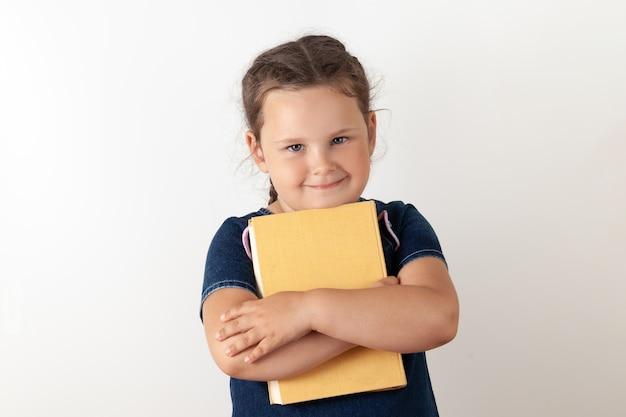Dziewczyna w niebieskiej dżinsowej sukience trzyma w rękach pomarańczową książkę i trzyma ją na piersi, patrząc w górę. uśmiechnięte dziecko, na białym tle