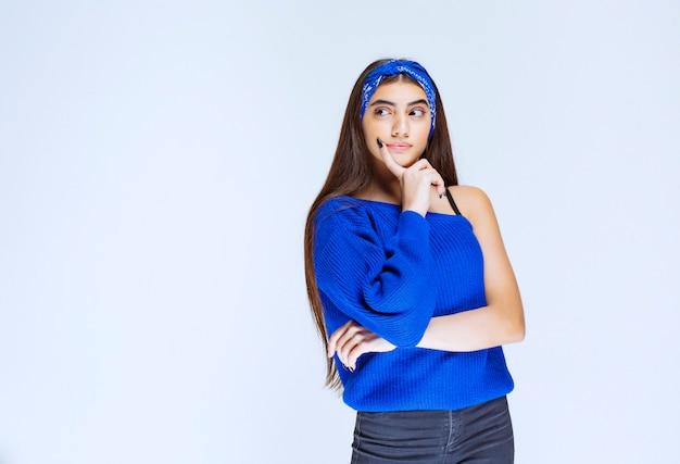 Dziewczyna w niebieskiej koszuli myśli i analizuje.