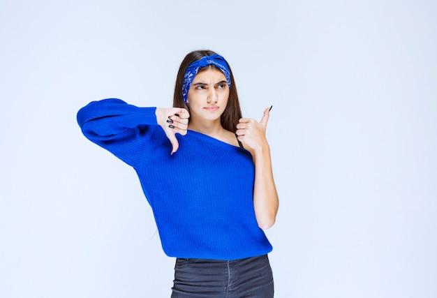 Dziewczyna w niebieskiej koszuli pokazano kciuk w górę iw dół znak.