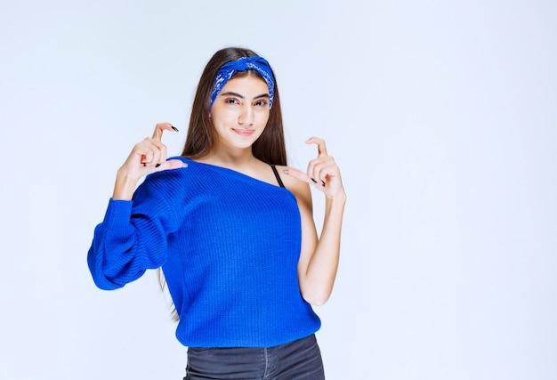 Dziewczyna w niebieskiej koszuli pokazująca rozmiar obiektu.