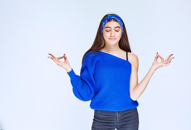 Dziewczyna w niebieskiej koszuli robi medytacji.