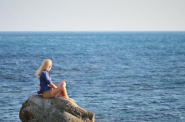 Dziewczyna w niebieskiej koszuli siedzi na skale i patrząc na morze