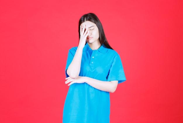 Dziewczyna w niebieskiej koszuli stoi na czerwonej ścianie i wygląda na zmęczoną i senną