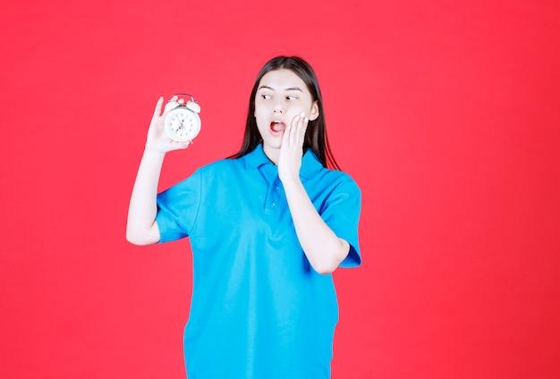 Dziewczyna w niebieskiej koszuli trzyma budzik i zdaje sobie sprawę, że jest spóźniona.