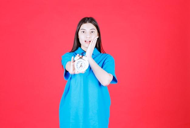 Dziewczyna w niebieskiej koszuli trzyma budzik i zdaje sobie sprawę, że się spóźnia