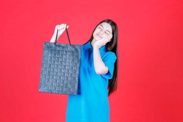 Dziewczyna w niebieskiej koszuli trzyma fioletową torbę na zakupy i wygląda na wyczerpaną.