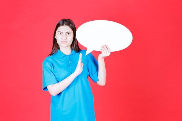Dziewczyna w niebieskiej koszuli trzyma owalną tablicę informacyjną i coś zatrzymuje