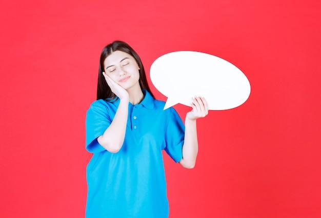 Dziewczyna w niebieskiej koszuli trzyma owalną tablicę informacyjną i wygląda na senną i zmęczoną