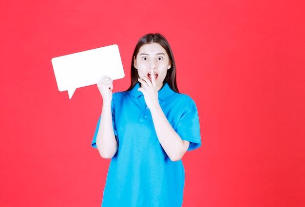 Dziewczyna w niebieskiej koszuli trzyma prostokątną tablicę informacyjną i wygląda na zaskoczoną i przerażoną