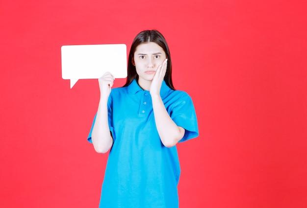 Dziewczyna w niebieskiej koszuli trzyma prostokątną tablicę informacyjną i wygląda na zdezorientowaną i zamyśloną