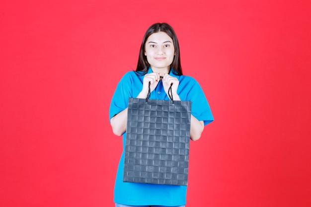 Dziewczyna w niebieskiej koszuli trzymająca fioletową torbę na zakupy
