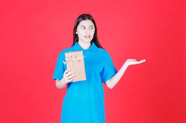 Dziewczyna w niebieskiej koszuli trzymająca kartonowe mini pudełko upominkowe i wzywająca kogoś, by podszedł i go zabrał