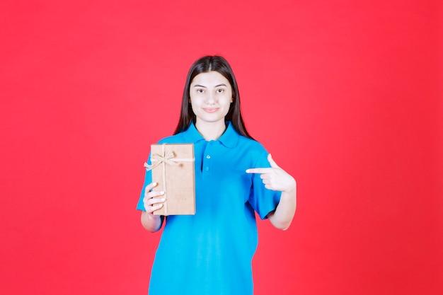 Dziewczyna w niebieskiej koszuli trzymająca kartonowe mini pudełko upominkowe