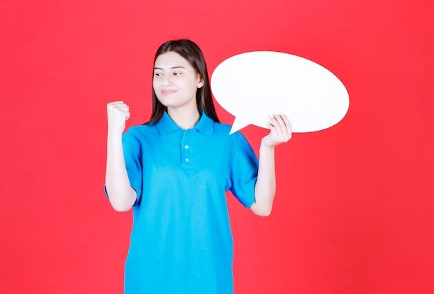 Dziewczyna w niebieskiej koszuli trzymająca owalną tablicę informacyjną i pokazującą pięść