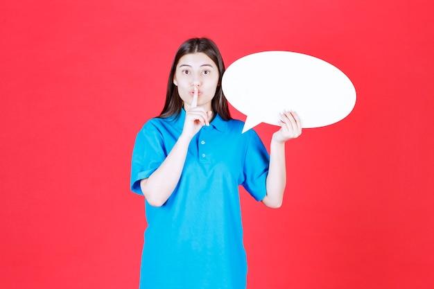 Dziewczyna w niebieskiej koszuli trzymająca owalną tablicę informacyjną i proszącą o ciszę