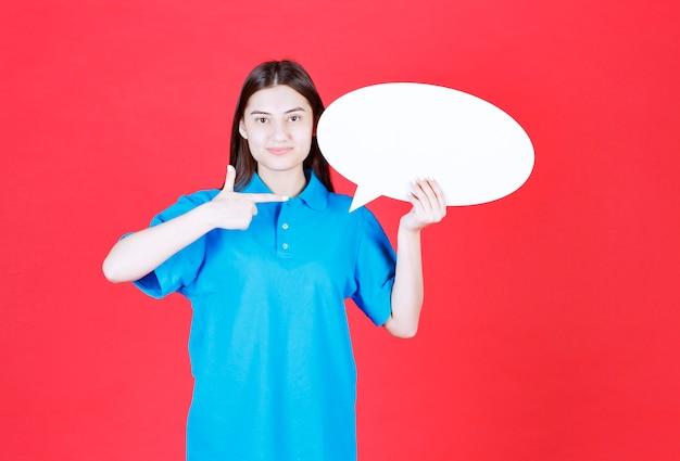 Dziewczyna w niebieskiej koszuli trzymająca owalną tablicę informacyjną