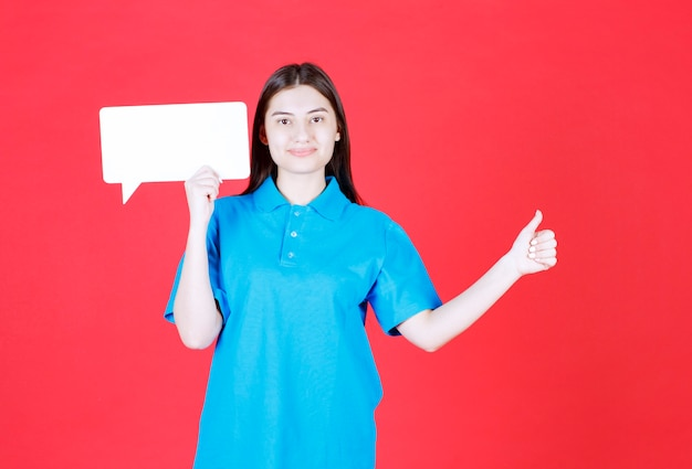 Dziewczyna w niebieskiej koszuli trzymająca prostokątną tablicę informacyjną i pokazująca pozytywny znak ręki