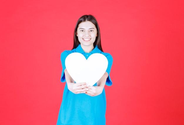Dziewczyna w niebieskiej koszuli trzymająca tablicę informacyjną w kształcie serca