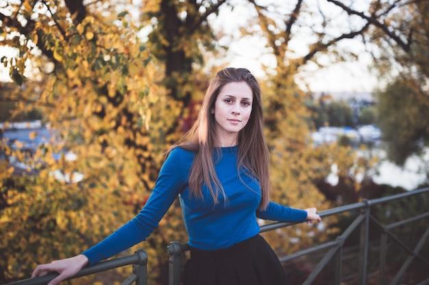 Dziewczyna w niebieskiej koszuli z długim rękawem i spódnicy na ulicy. jesienny czas.