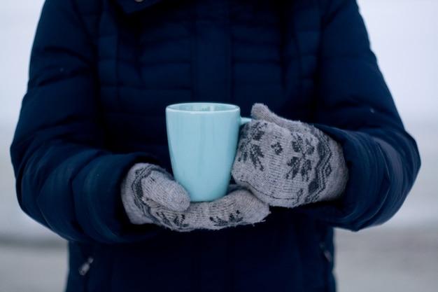 Dziewczyna w niebieskiej kurtce puchowej i rękawiczkach trzyma niebieską filiżankę herbaty