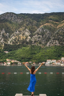Dziewczyna w niebieskiej sukience stoi z rękami w górze na molo na tle zatoki kotorskiej w czarnogórze. ładne i przytulne miasto.