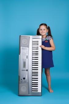 Dziewczyna w niebieskiej sukience trzyma pionowy syntezator elektroniczny