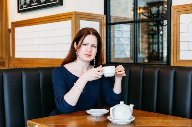 Dziewczyna w niebieskiej sukience z długimi włosami w kawiarni, czeka na przyjaciół, herbatę, pieczenie