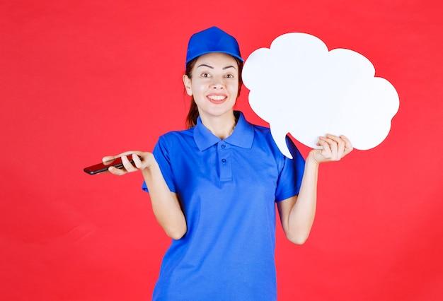 Dziewczyna w niebieskim mundurze i berecie trzymająca białą pustą tablicę dyskusyjną i prowadzącą spotkanie online lub wysyłającą wiadomość audio.