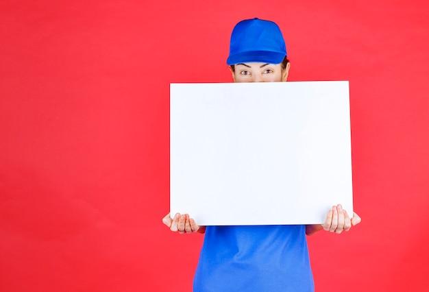 Dziewczyna w niebieskim mundurze i berecie, trzymająca biurko informacyjne w białym kwadracie i czująca się pozytywnie.