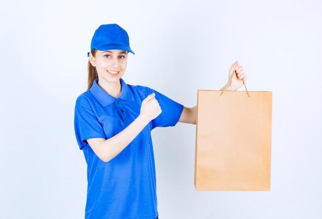 Dziewczyna w niebieskim mundurze trzyma kartonową torbę na zakupy i pokazuje jej pięść.