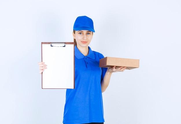 Dziewczyna w niebieskim mundurze trzyma kartonowe pudełko na wynos i listę klientów.