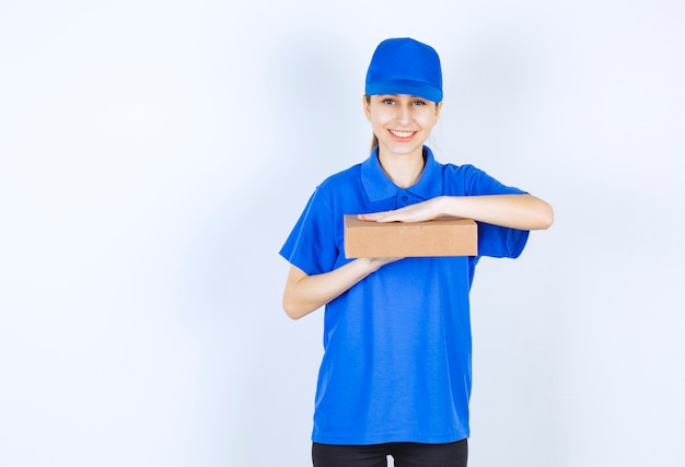Dziewczyna w niebieskim mundurze trzyma kartonowe pudełko na wynos.