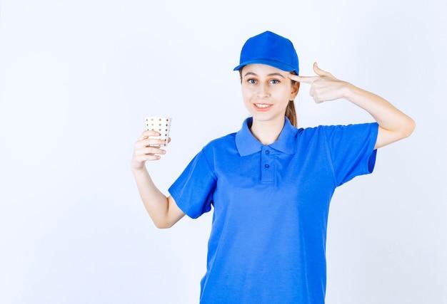 Dziewczyna w niebieskim mundurze trzyma kubek napoju i myśli lub ma nowy pomysł.